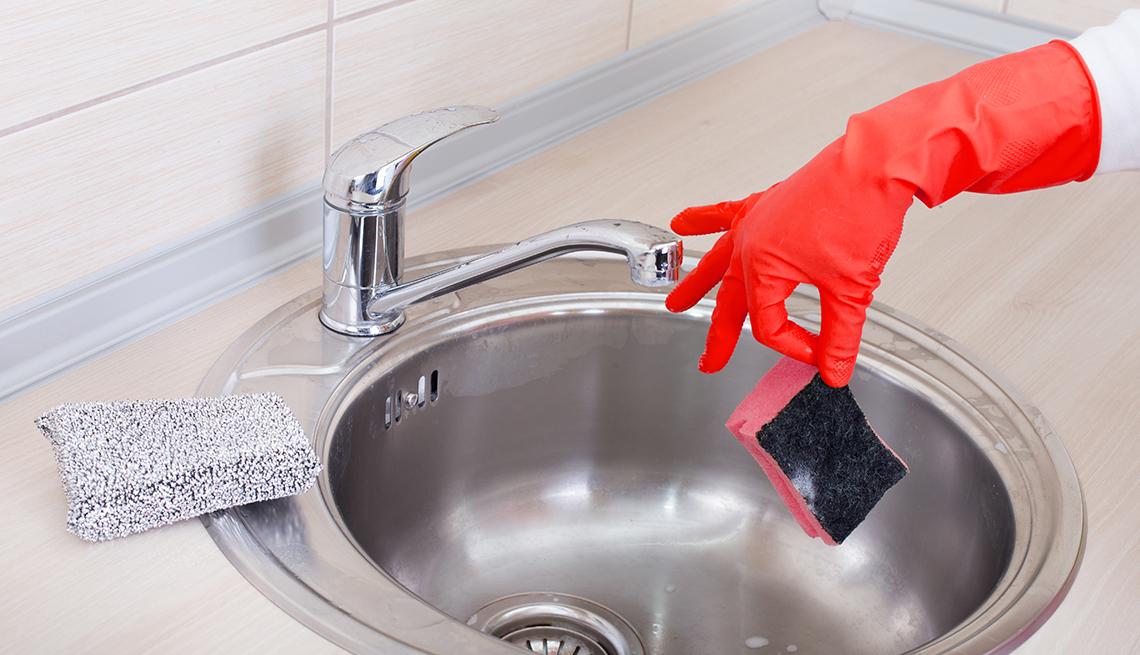 Fregadero y mano con guante sosteniendo una espoja de fregar vieja