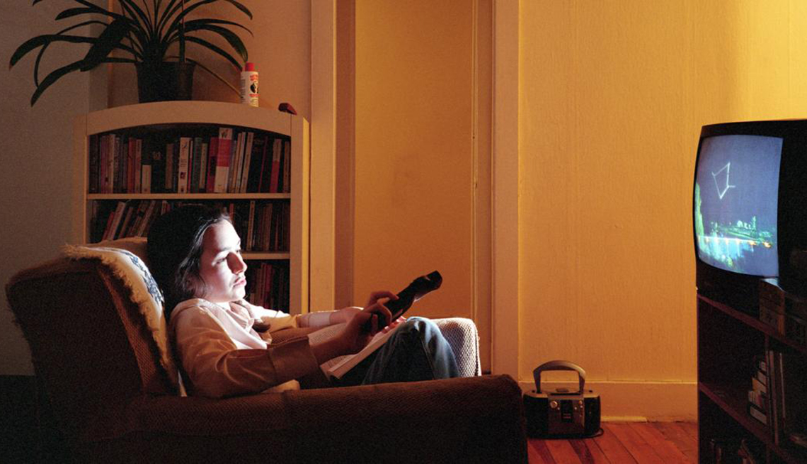 Young woman using television with a remote control, Coach Potato Syndrome, Healthy Living