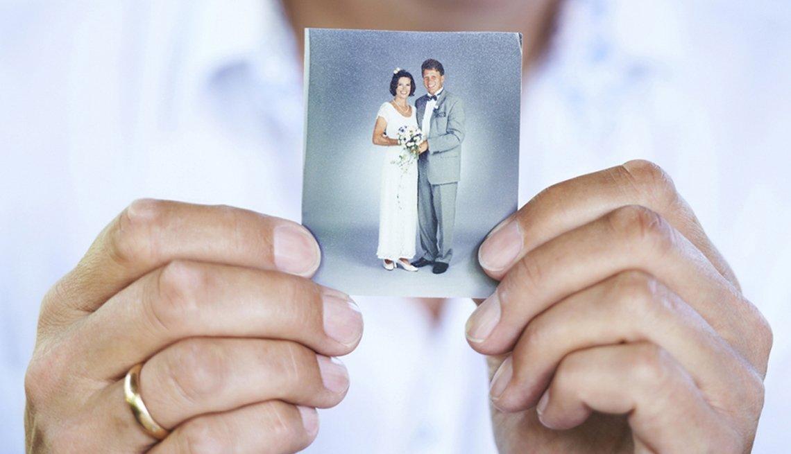 Mano sosteniendo foto de pareja recién casada