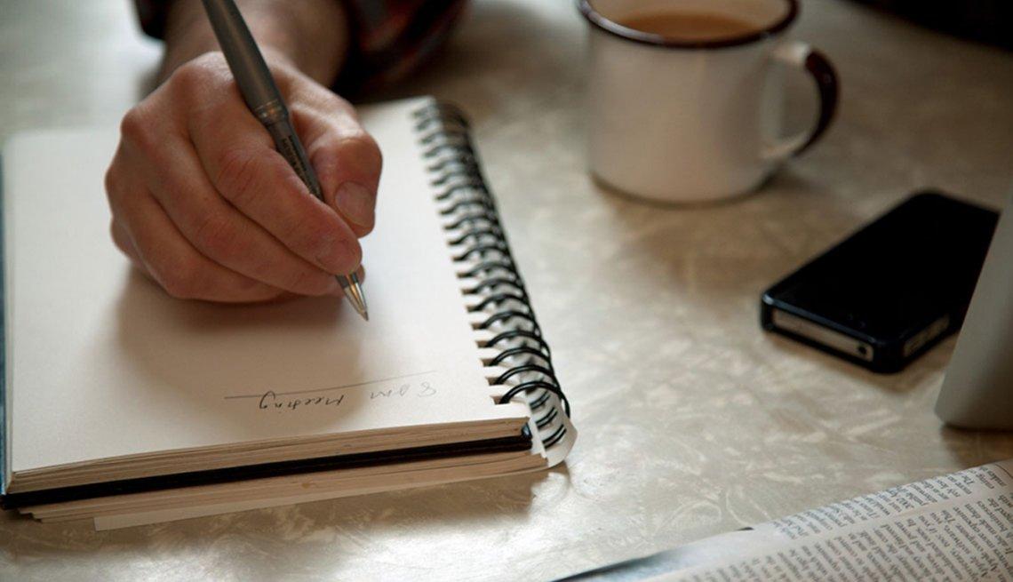 Mano sosteniendo un lápiz sobre un cuaderno