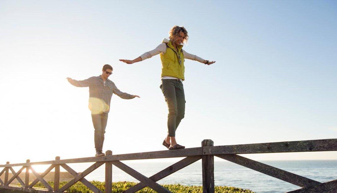 Pareja camina balanceándose sobre una valla
