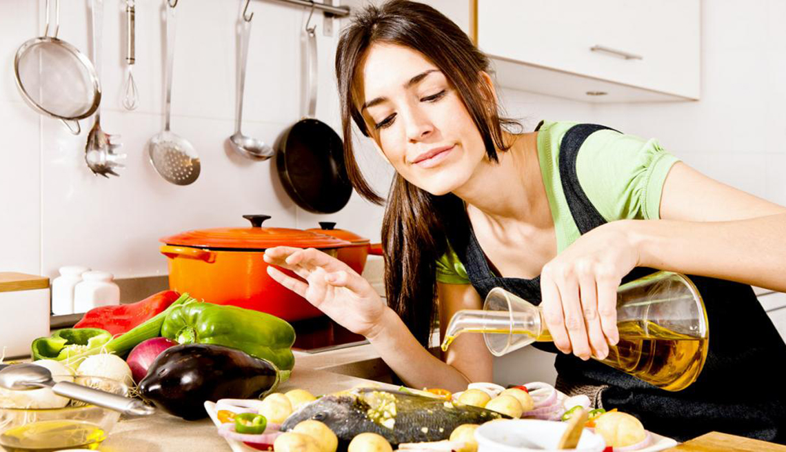 A Woman Pouring Oil over fish while Cooking, Good Fats, Healthy Living
