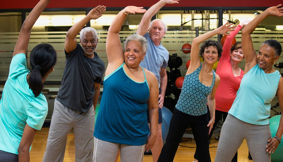 group of smiling people stretching arm overhead in a gym exercise class