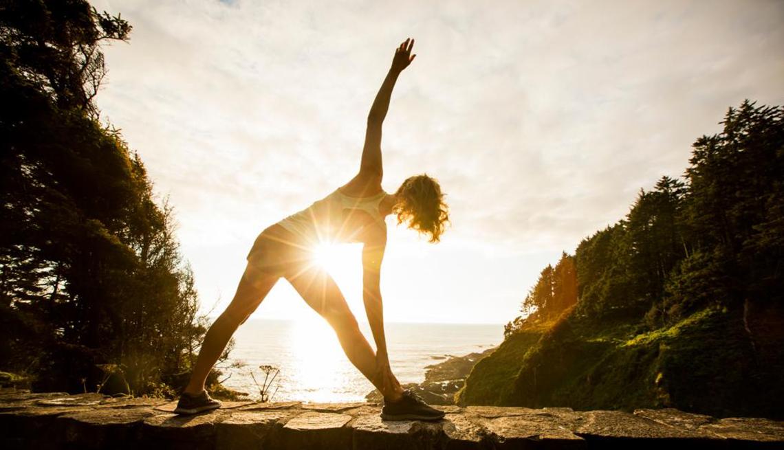 Mujer a contraluz de amanecer haciendo ejercicio