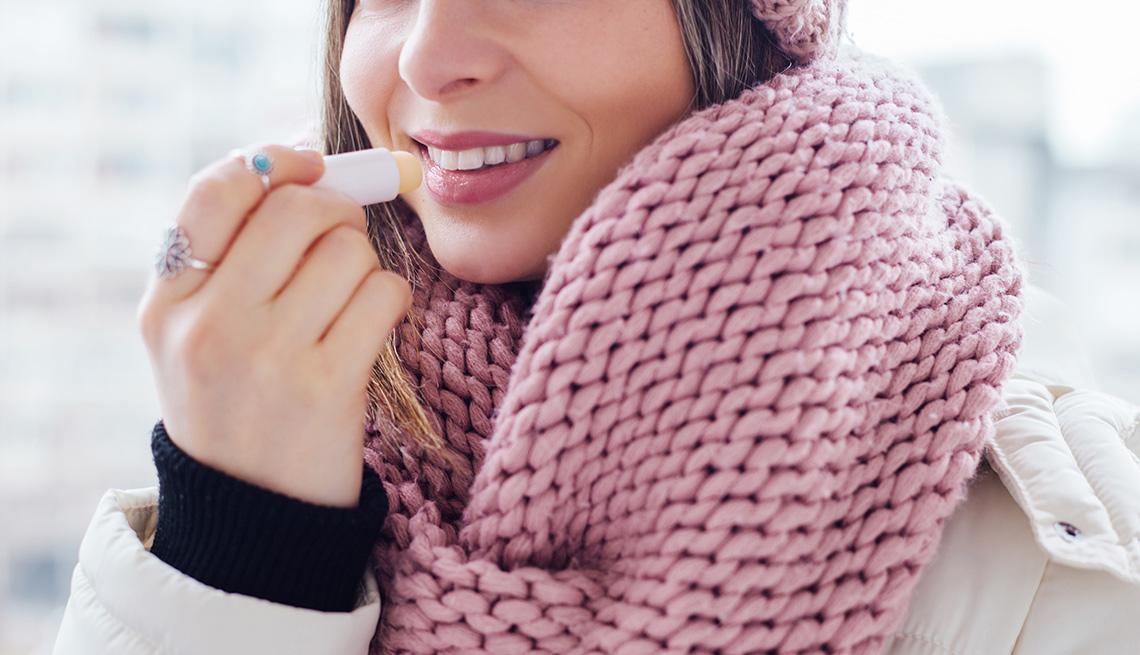 Mujer untándose un bálsamo en los labios