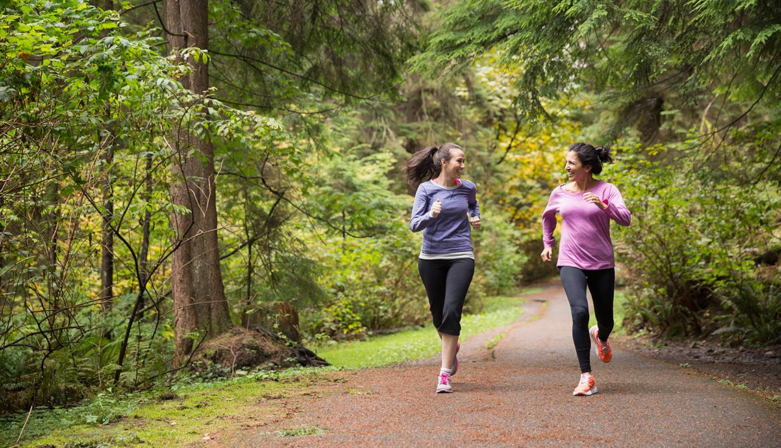 Dos mujeres corriendo por un camino forestal