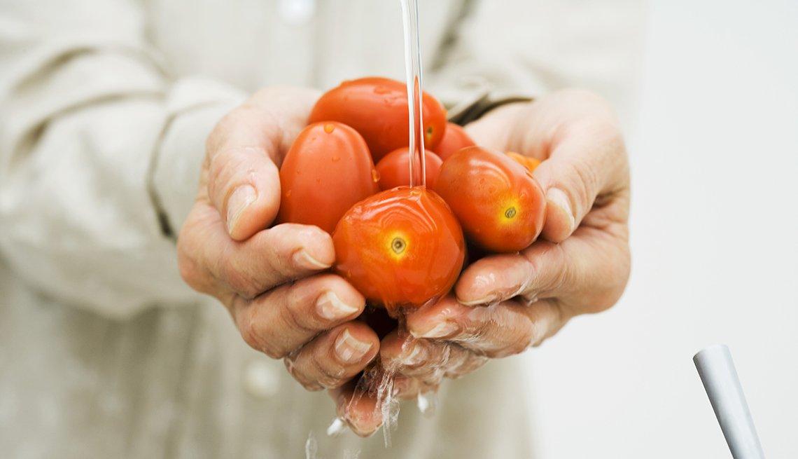 Mujer lavando unos tomates