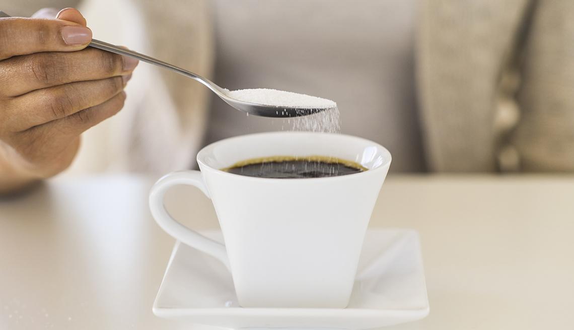 Mujer endulzando su café con azúcar refinada.