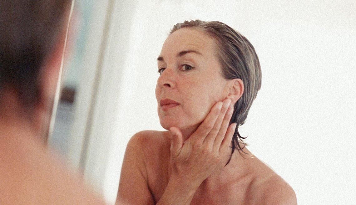 Mujer de mediana edad observando la piel de su cara