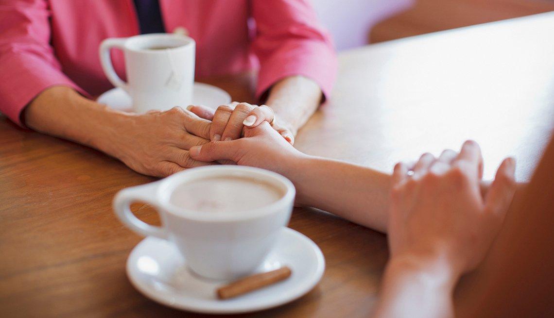 Amigas tomadas de la mano y tomando café