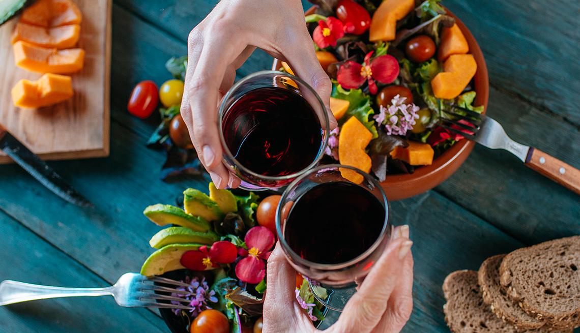 Manos con una copa de vino brindando