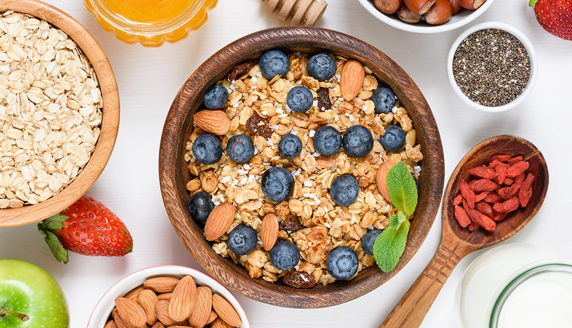Granola con moras azules y otros alimentos alrededor