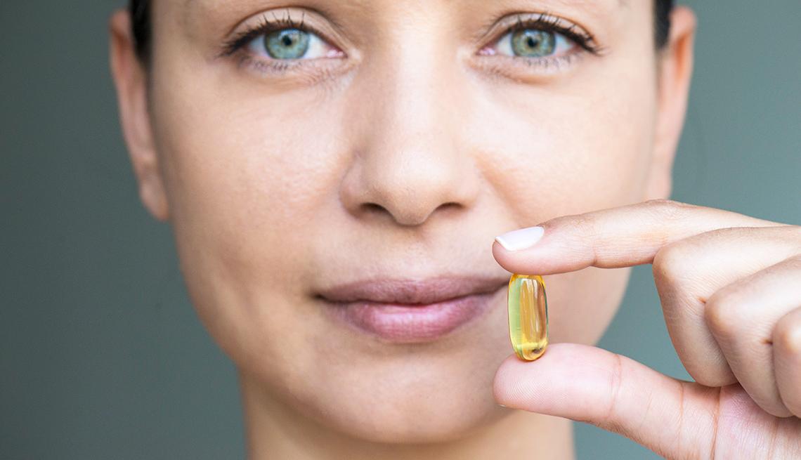 A woman holds a transparent yellow gel pill