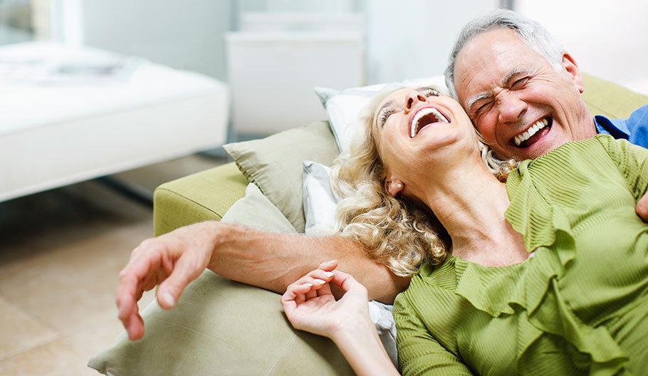couple laughing while sitting on a couch