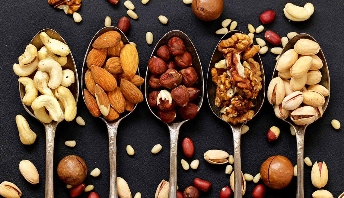 various kinds of nuts, including cedar, cashew, hazelnuts, walnuts, in spoons