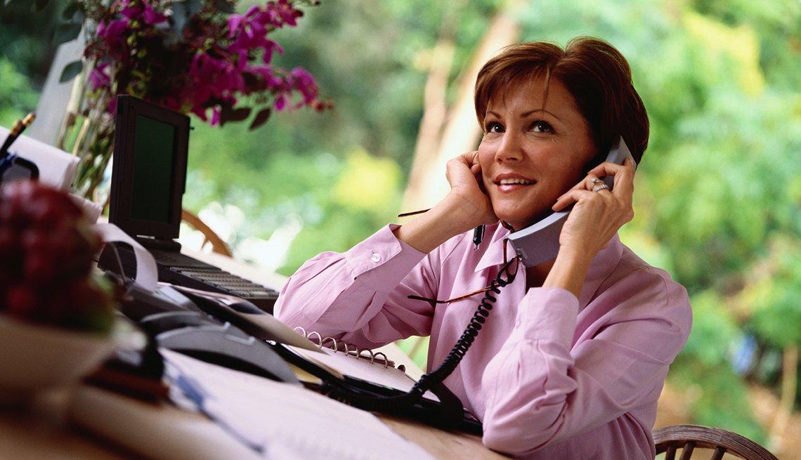 Mujer con blusa rosa hablando por teléfono en su escritorio
