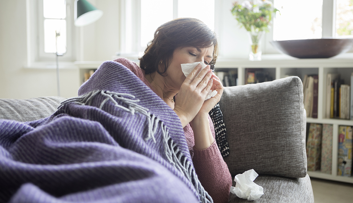 Woman blowing nose under blanket, laying on couch