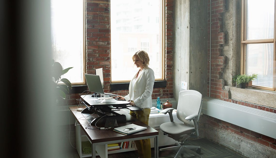 Businesswoman using computer sit-stand desk in office