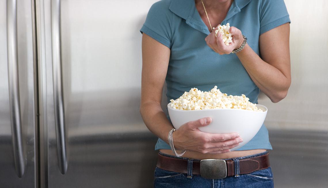 Mujer sostiene un puñado de palomitas de maíz en una mano y en la otra un recipiente blanco con el resto de las palomitas.