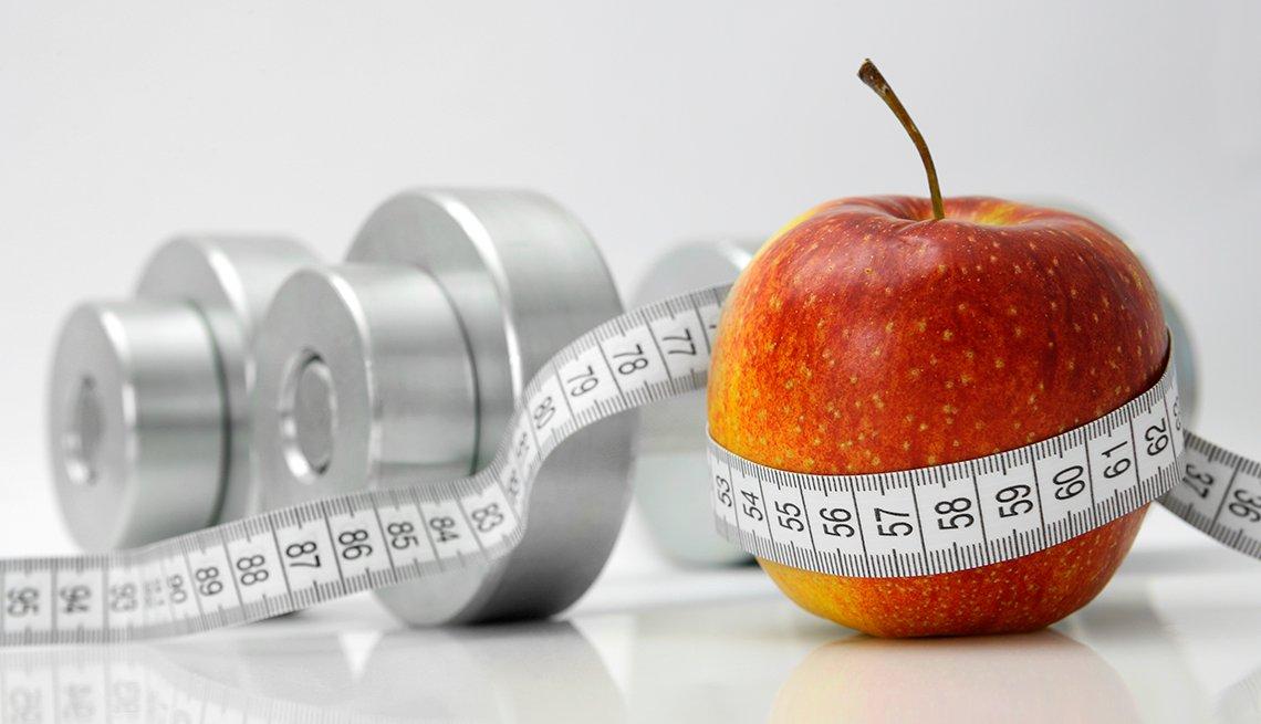 Mancuernas, cinta métrica y una manzana.