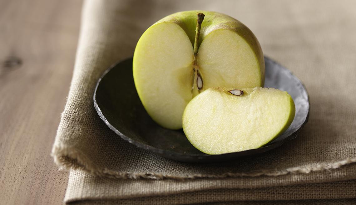 Una rebanada de manzana junto a la mitad de la manzana en un paño doblado sobre una mesa de madera.