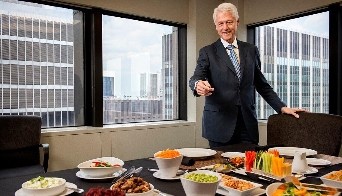 Bill Clinton sonríe y apunta hacia la mesa con platos de vegetales.