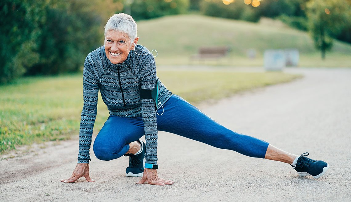 Smiling senior sports woman exercising in the park
