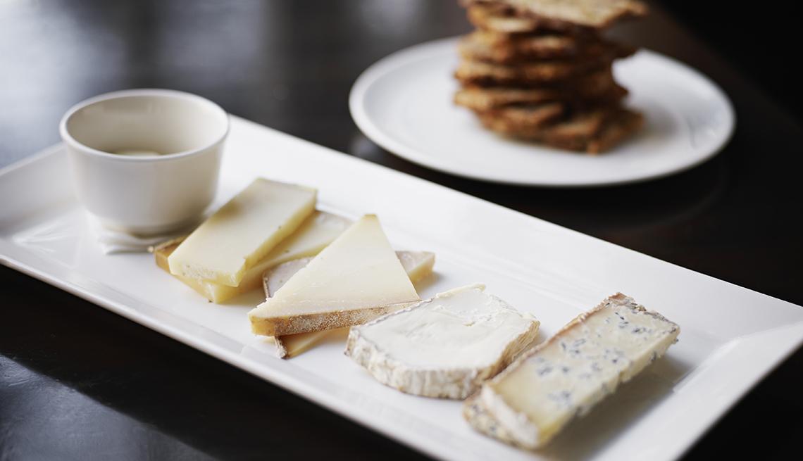 Rebanadas de queso en un plato blanco rectangular con unas galletas en otro plato.