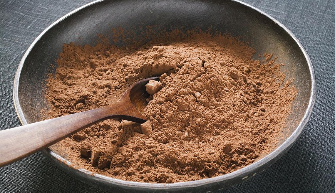 Un tazón de cacao en polvo con una cuchara de madera.