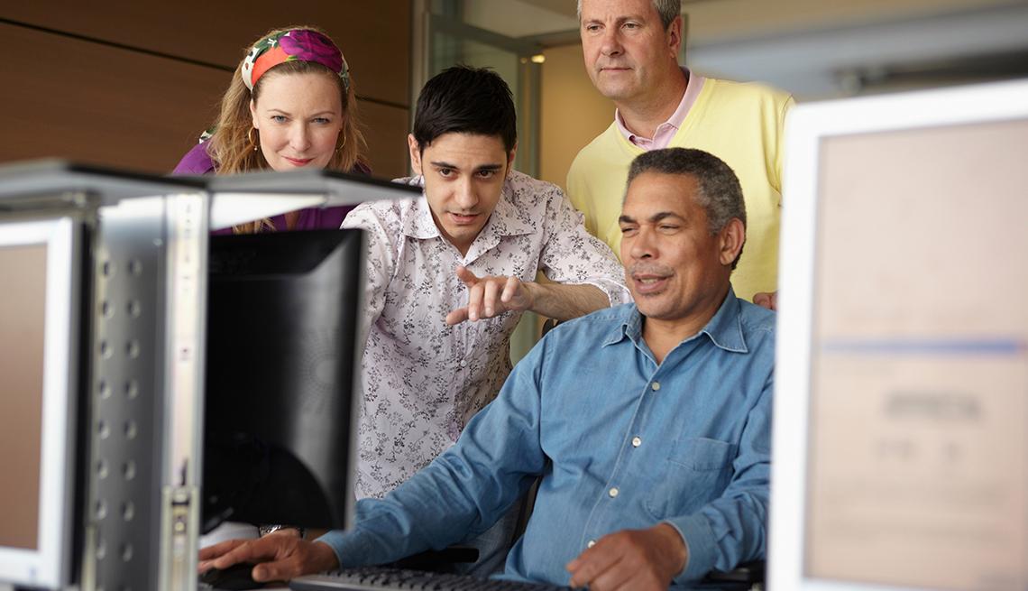 Joven explica y apunta a la pantalla de una computadora mientras un hombre mira. Una mujer y otro hombre también miran a la computadora.