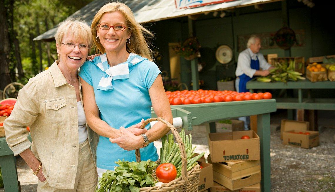 Dos mujeres en el mercado de agricultores con cesta de verduras y tomate.