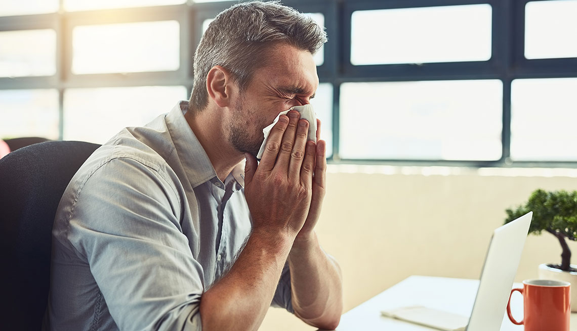 mature man sneezing in his office