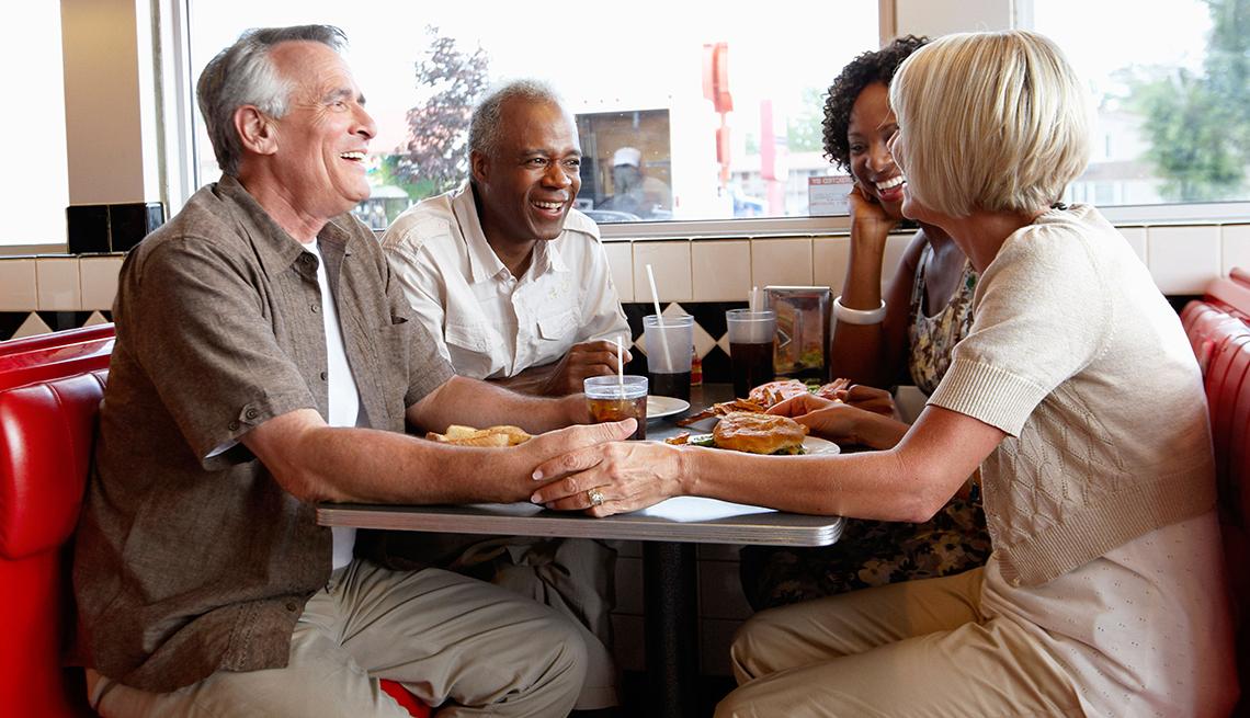 Dos parejas conversan y sonríen durante una comida.