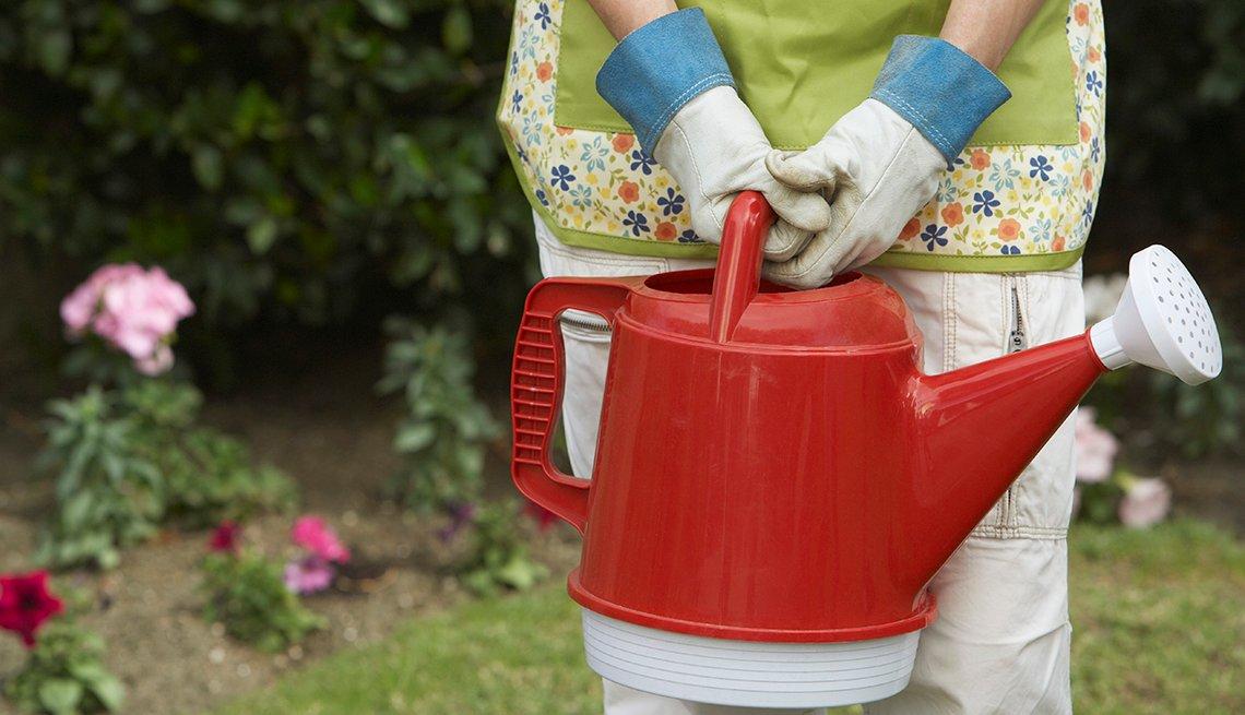 Mujer con guantes y regadera de agua en el jardín.
