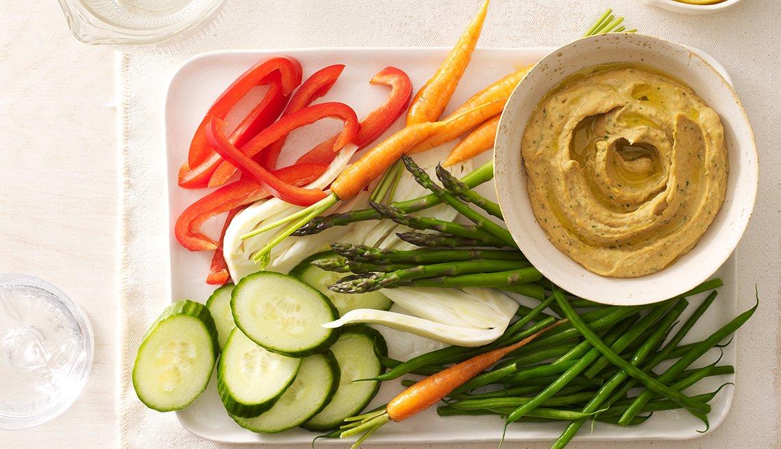 Hummus en plato de vegetales crudos.