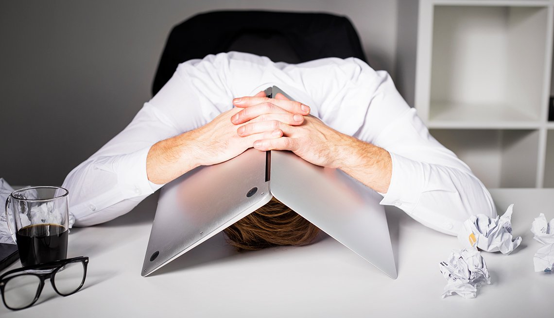 A man hides his head underneath his laptop