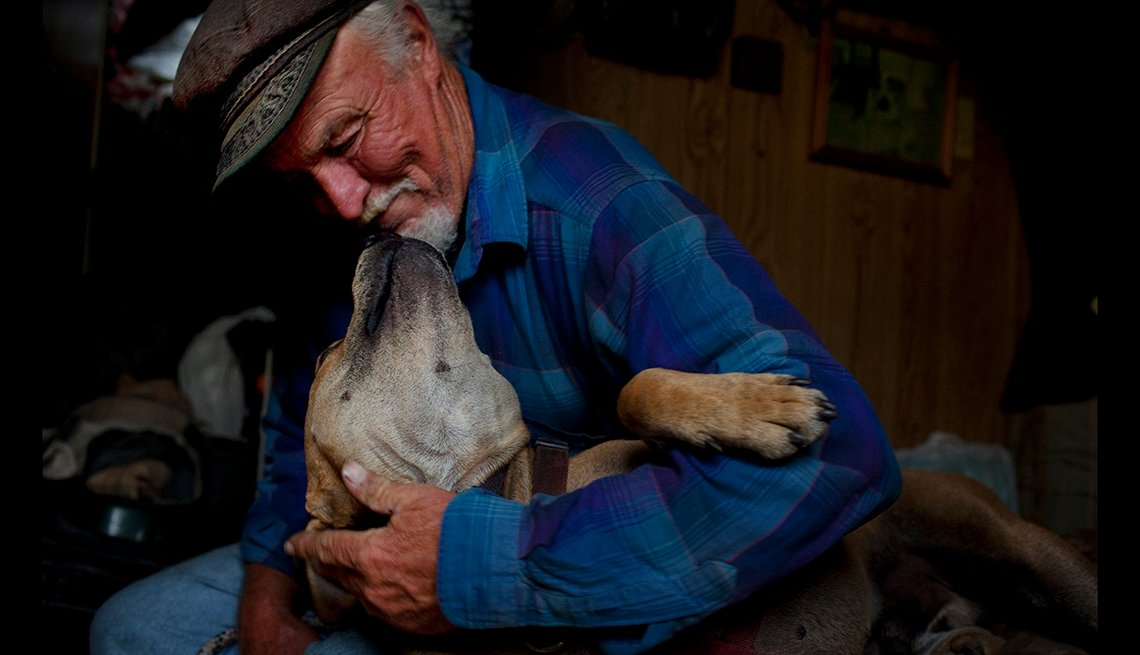 Hombre blanco acariciando a su perro.