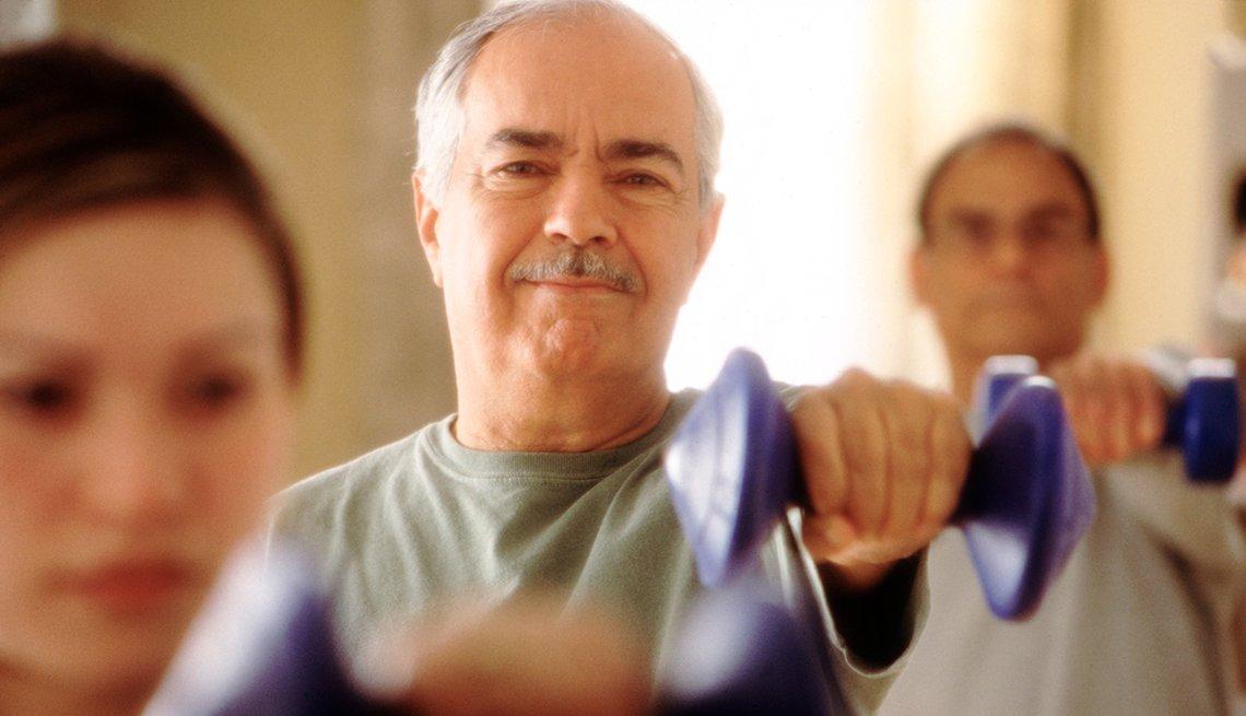 Hombre mayor levantando una mancuerna o pesa en una clase de aeróbicos.