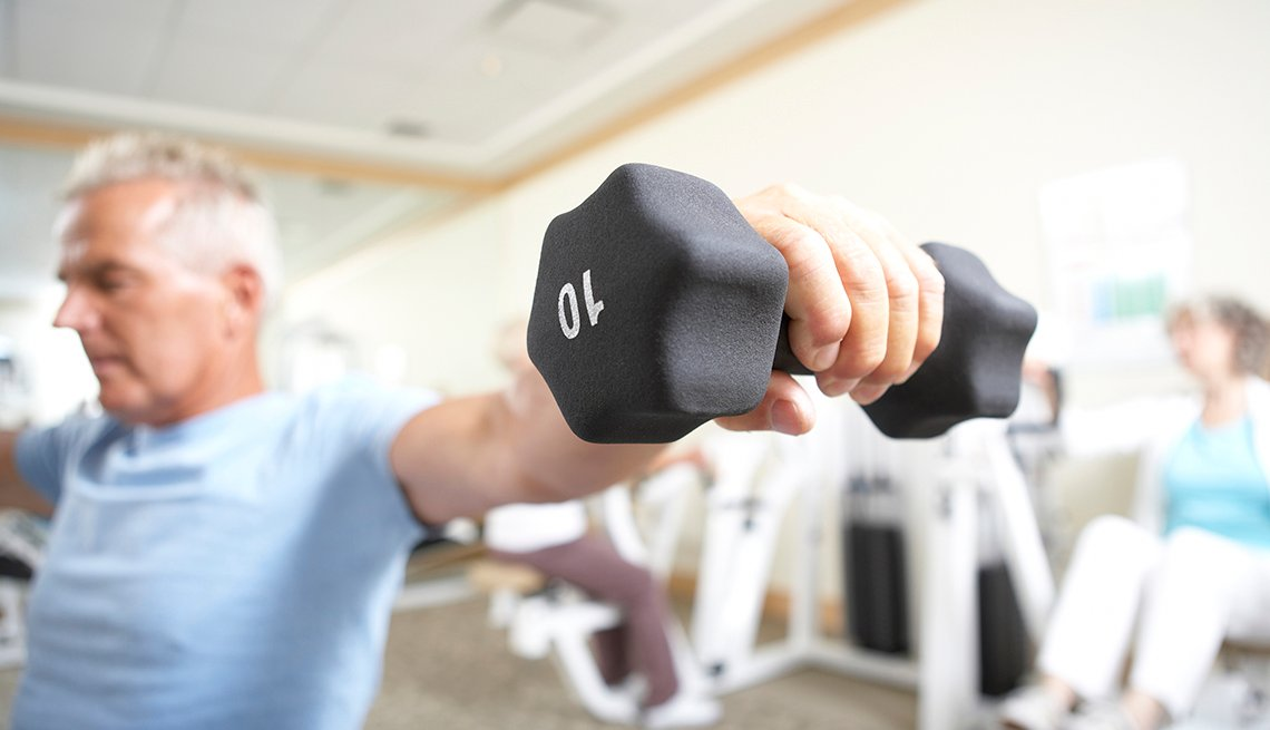 Hombre levanta pesas o mancuernas de 10 libras en un gimnasio.