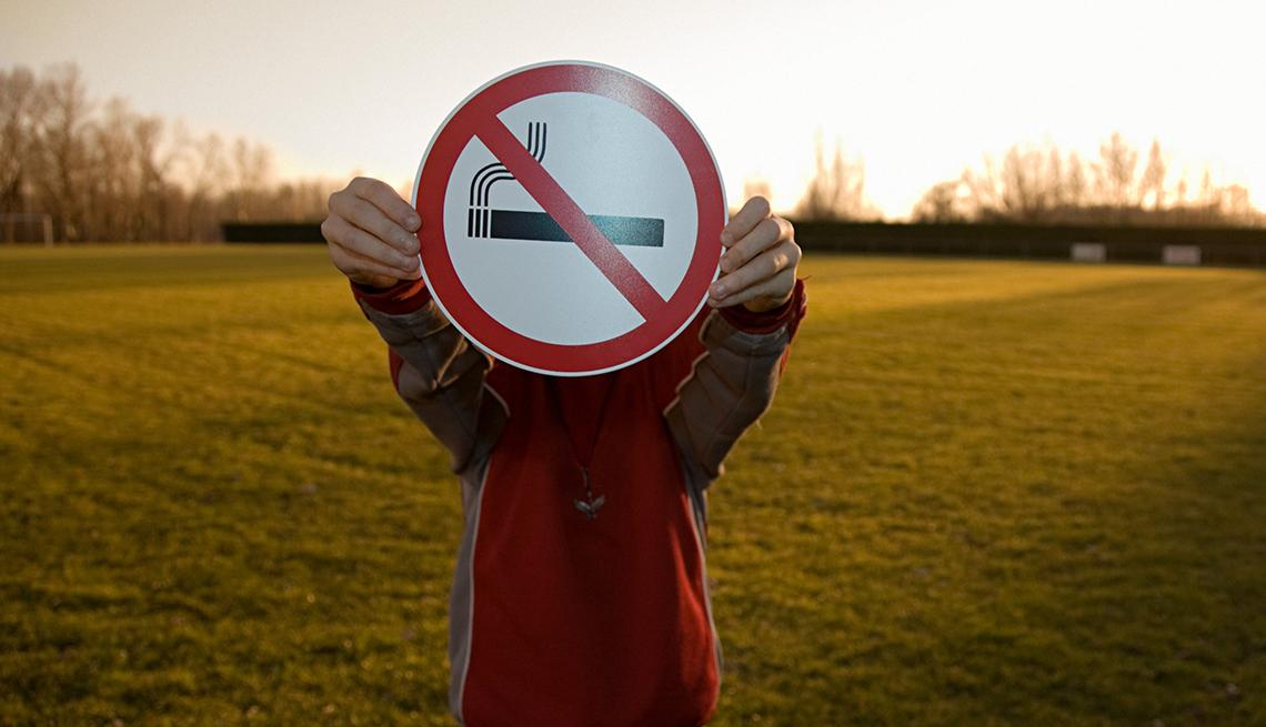 Persona sostiene un símbolo de no fumar.
