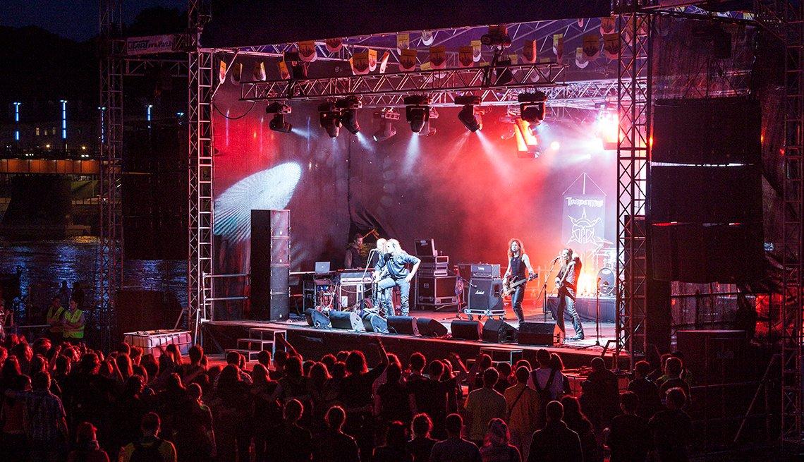 Escenario iluminado mientras una banda toca.