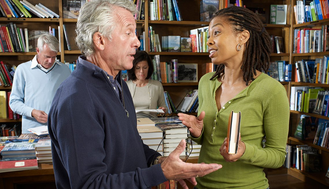 Hombre y mujer con libro en la mano conversan en una librería.
