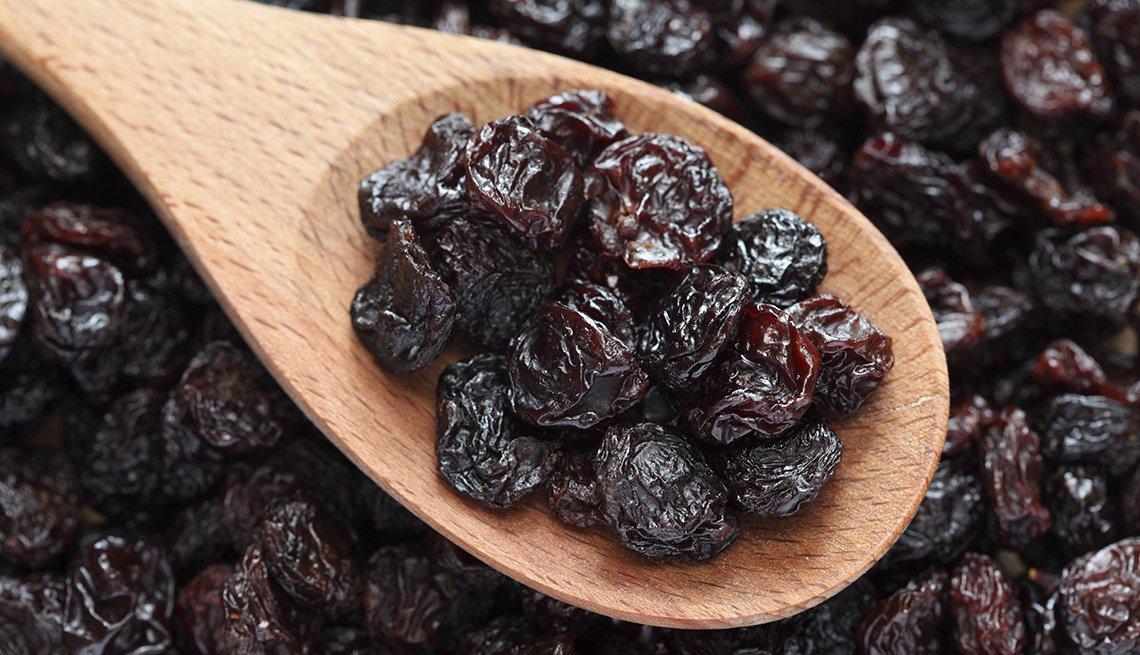 Pasas uva en una cuchara de madera.