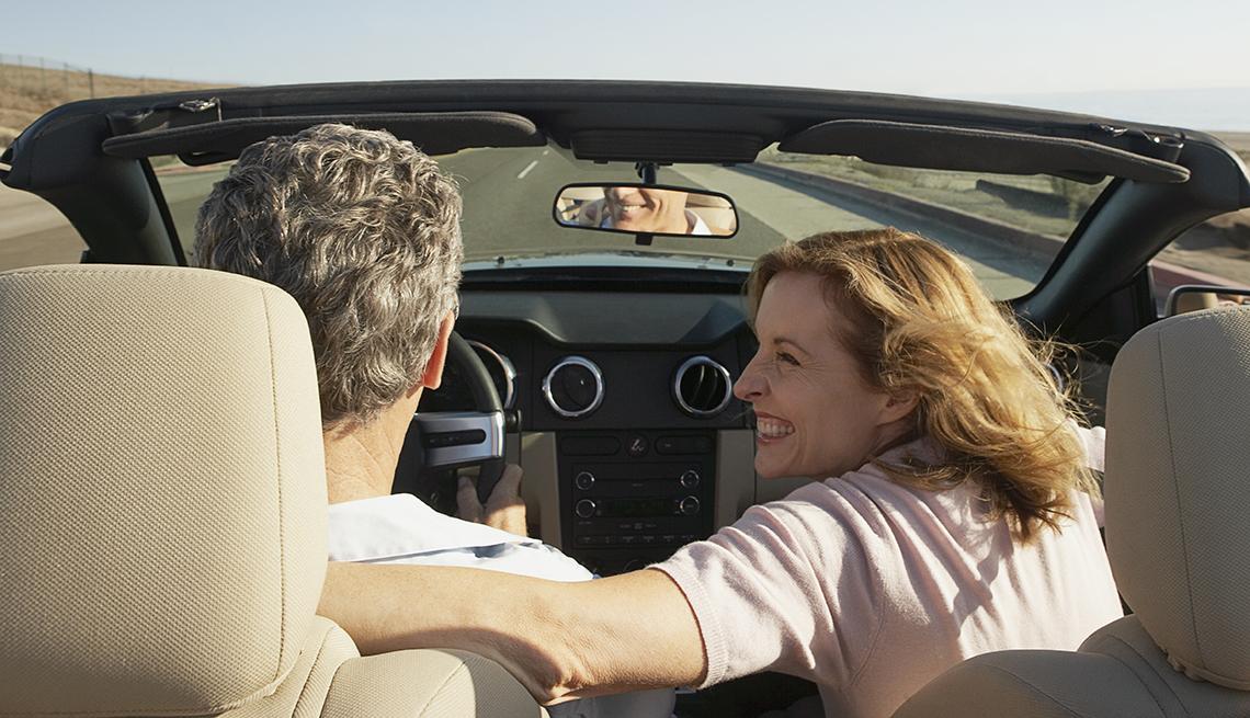 Una mujer en el asiento de pasajero sonríe a un hombre que maneja un auto convertible.