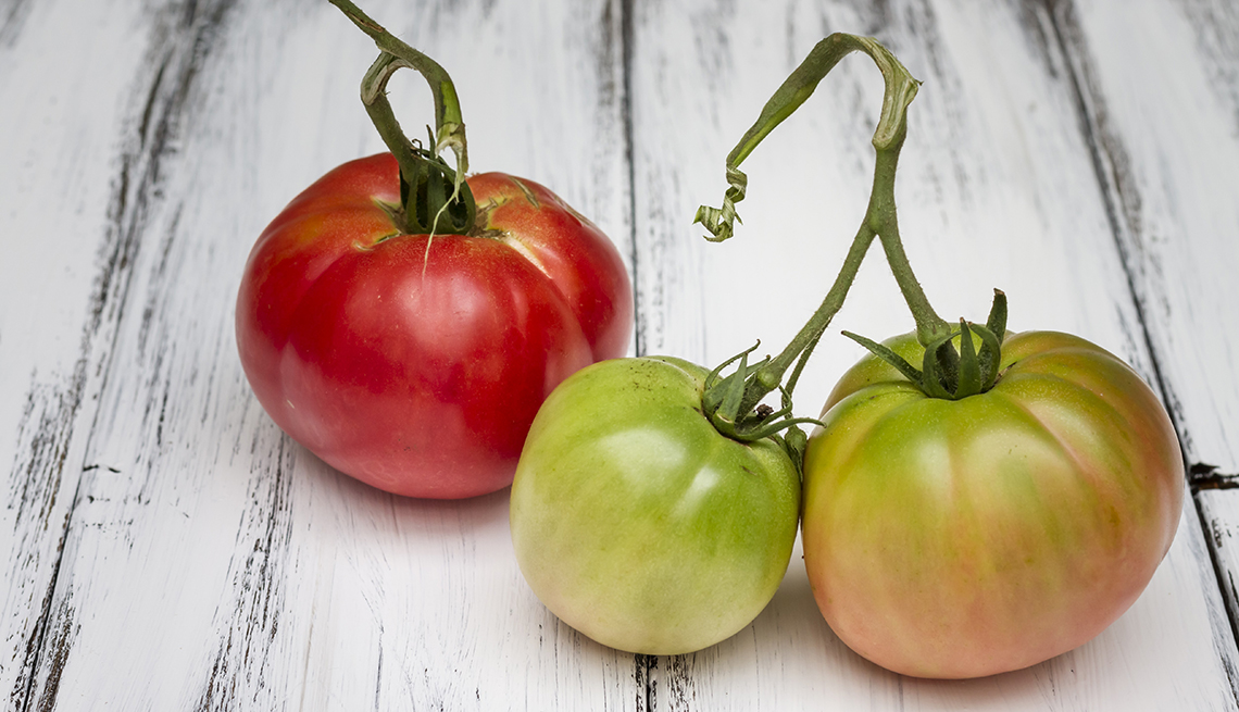 Tres tomates en diferente color encima de una mesa de madera.