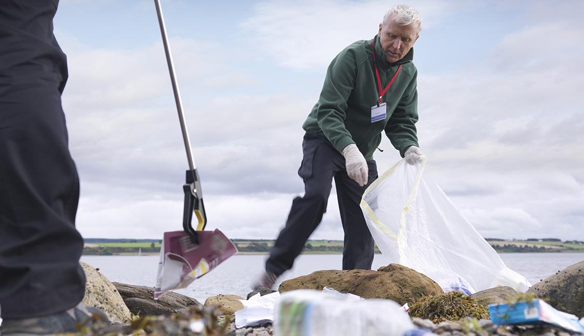 Voluntario trabaja con otros recogiendo basura cerca de una playa o lago.