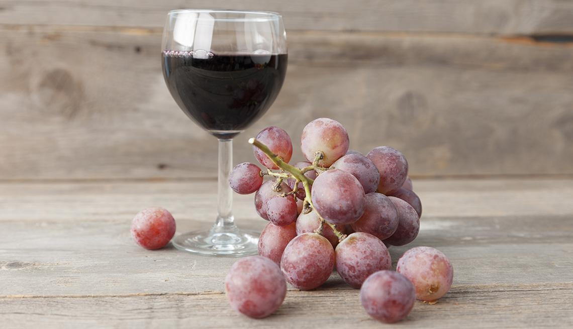 Uvas rojas y vaso de vino tinto sobre una mesa de madera.