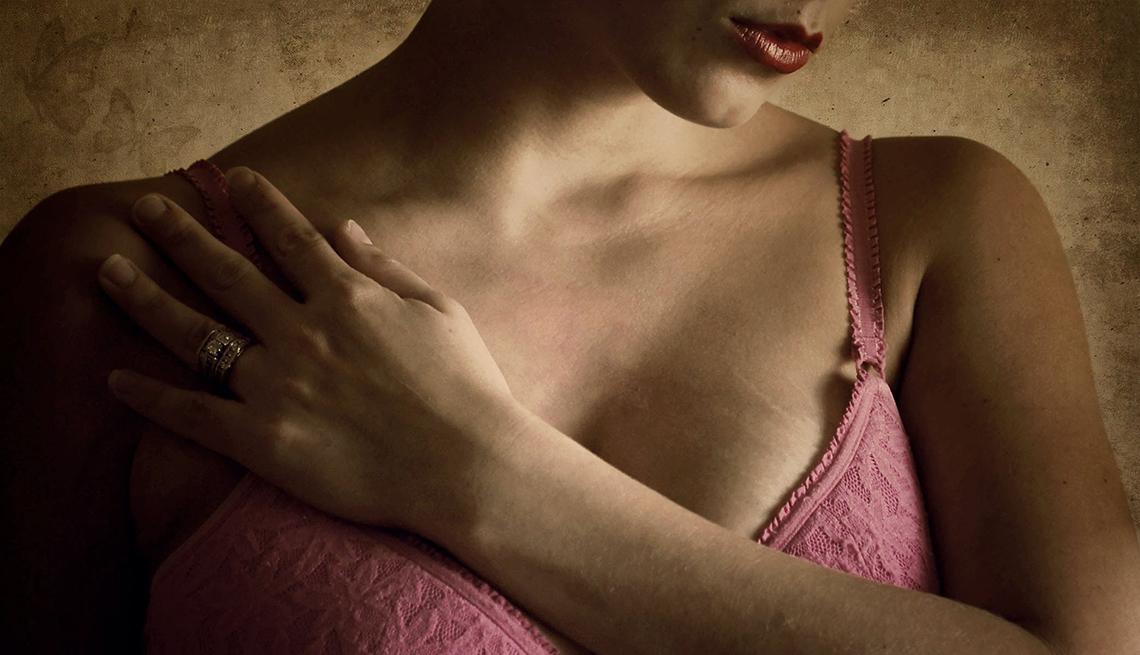 Mujer en ropa interior coloca su mano sobre su pecho.