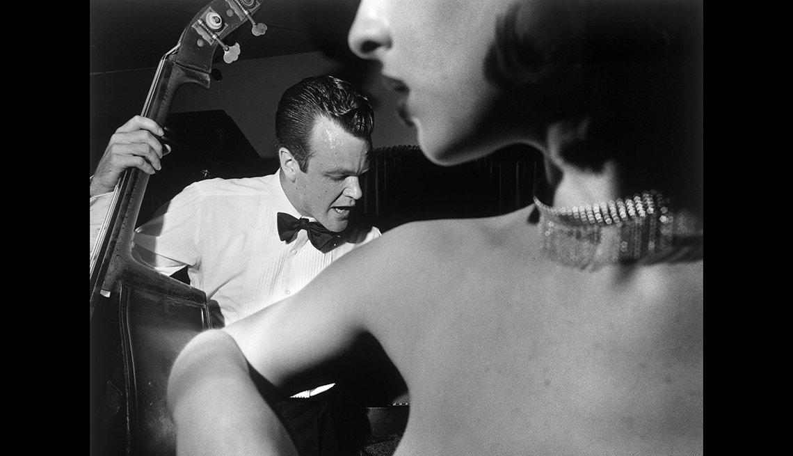Hombre tocando instrumento musical y mujer lo escucha.