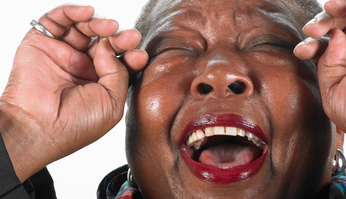 Mujer afro-america riéndose a carcajadas.